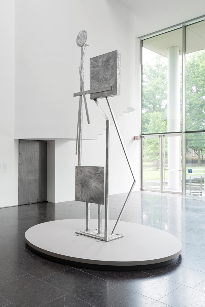 Photo: David Stover © Virginia Museum of Fine Arts May 22, 2015 David Smith: L2015.5 Here and Above: A Dialogue Between Sculptures Through March 2016 A year-long installation in the museum's atrium, Here and Above situates two welded steel sculptures in a cross-generational dialogue about material, form, and the environment. Rising from the ground in a delicate balance, Two Box Structure reads as a vertical composition of geometric shapes, while also suggesting human figures. Extending from the wall overhead, Noctilucent Clouds offers a literal model of luminous, thin clouds located in the most distant part of the atmosphere, while also reading as a dynamic composition of lines in space. Rebecca Smith (b.1954), the daughter of Abstract Expressionist sculptor David Smith (1906–1965), spent her early childhood in the New York hamlet of Bolton Landing, playing in the fields amid dozens of her father's sculptures. Here the works of these two artists respond to one another as natural light activates their surfaces, drawing the surrounding space into the conversation. Rebecca Smith American, born 1954 Noctilucent Clouds, 2015 Stainless steel, interference acrylic paint On loan from Rebecca Smith, courtesy Waqas Wajahat David Smith American, 1906-1965 Two Box Structure, 1961 Stainless steel On loan from Philadelphia Museum of Art: Gift of Paul and Hope Makler, 1972