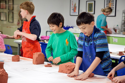 Kids work with clay in a studio class.