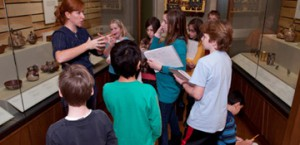 A group of children listen to an instructor in the galleries.